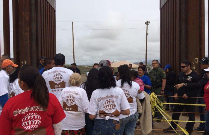 Se abrazan más de mil personas en muro fronterizo