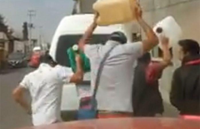Bailan Payaso de rodeo con garrafones en fila de gasolinera