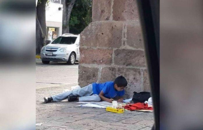 Niño hace tarea mientras su mamá vende mazapanes en la calle; tiene promedio de 9