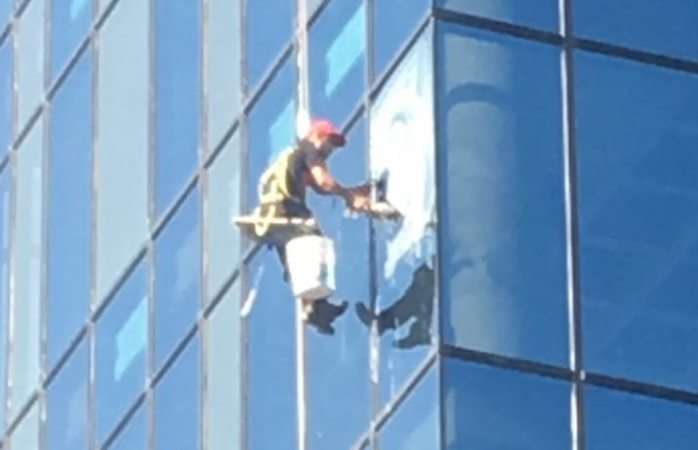 Sorprende limpia vidrios en el quinto piso de local en el distrito 1