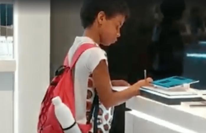 Niño usa tablet de exhibición en tienda comercial para hacer su tarea