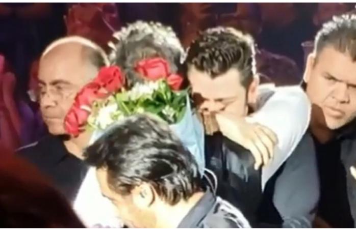 Alejandro Fernández recibe flores de un hombre durante concierto