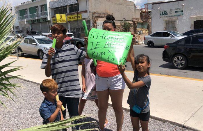 Tu familia te necesita, baja por favor: pancarta de sus hijos